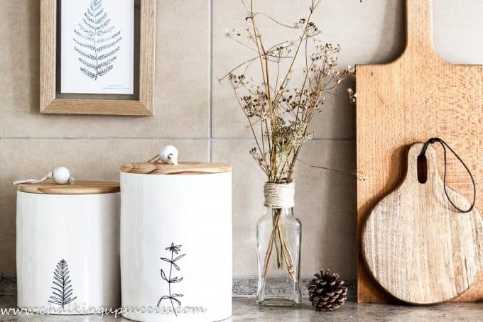The kitchen counter decorated for the autumn home tour. Wooden chopping boards, white and wood containers and a glass bottle filled with dried flower-heads.