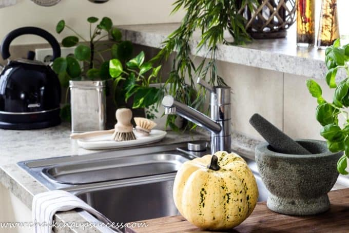 The kitchen  decorated for the autumn home tour. Aliminium sink, chopping board, small yellow speckled pumpkin and a pestle and mortar.