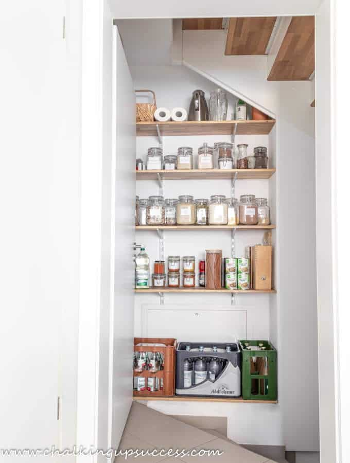 A small understairs pantry in the kitchen. Organized with glass spring top containers, labeled.