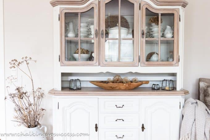 A white and wood painted hutch decorated for the autumn home tour with a longe wooden bowl filled with pinecones, acorns and Alium seedheads.