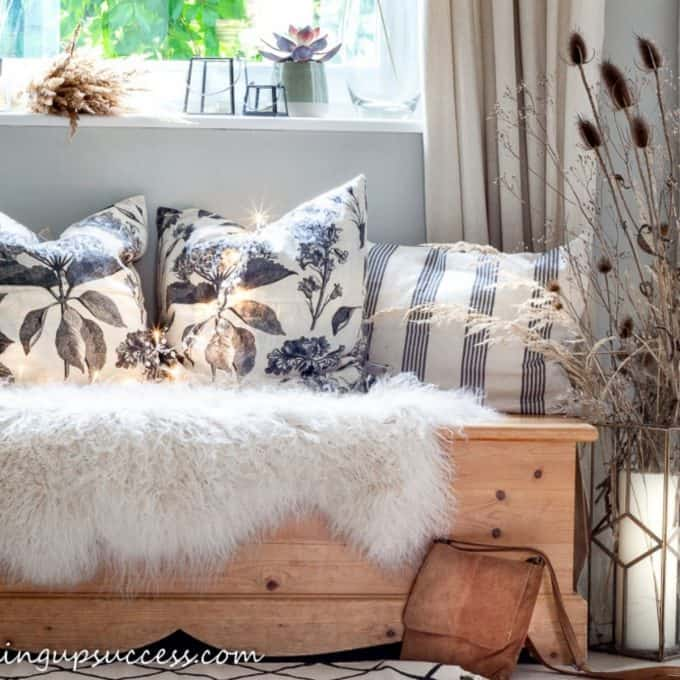 A pine bench covered with cushions and sheepskin rugs.