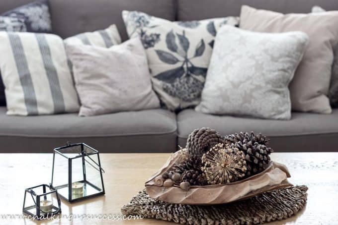 Natural decorating for the Fall home tour. A large wooden bowl in the shape of a leaf sits on the coffee table and contains pine cones and acorns.
