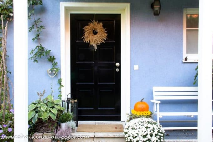 Starting this autumn home tour at the front door - black front door decorating with a grass wreath