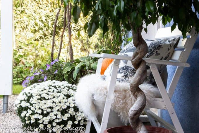 Home tour seating outside the front door. White wooden bench decorated with a sheepskin and linen cushions.