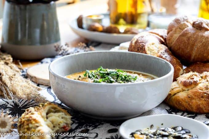 Close-up of a bowl of spicy pumpkin soup on a table with rustic bread rolls
