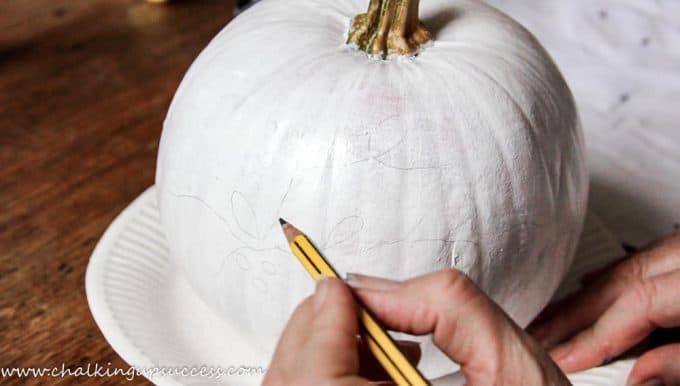 Pencilling a design onto a white pumpkin - pretty painted pumpkin ideas