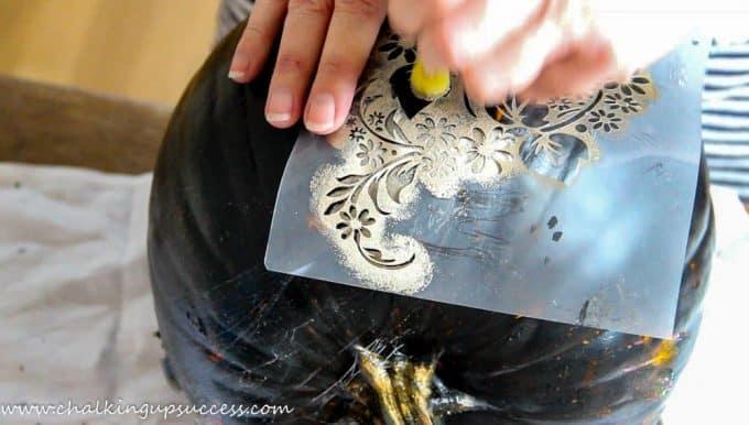 Using a stencil to create a floral design on a black pumpkin