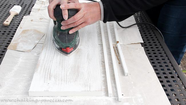 A person using an electric sander to remove white chalk paint on a piece of wood