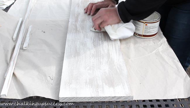 A person rubbing white way into a piece of painted wood