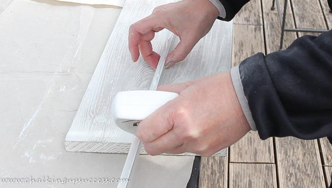 A person applying wood glue to the wood trim of a pedestal tray