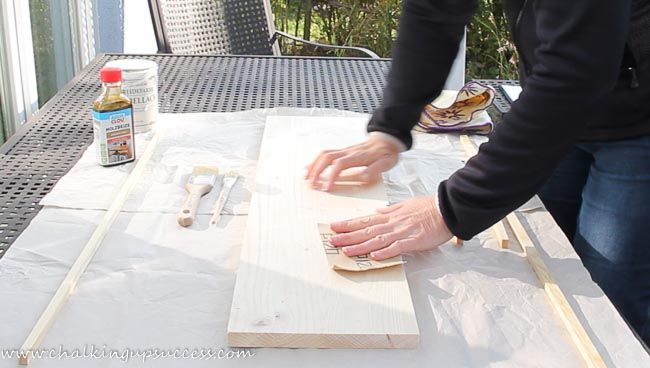 A person using sandpaper on a piece of wood
