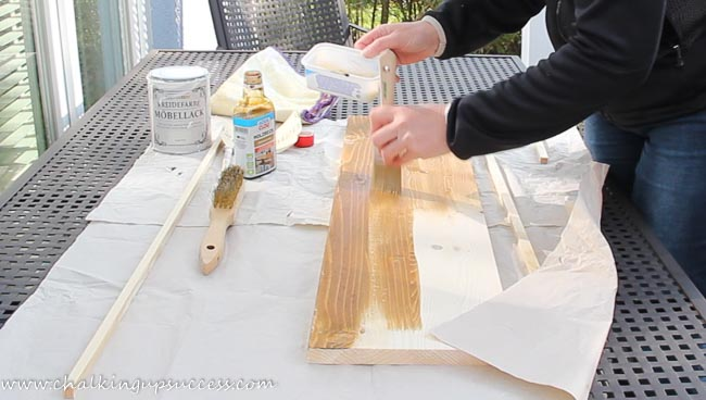 A person painting a piece of wood with walnut woodstain