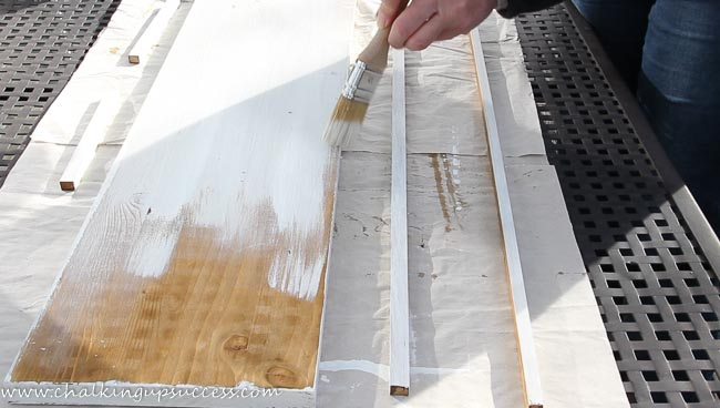 A person painting a piece of wood with white chalk paint