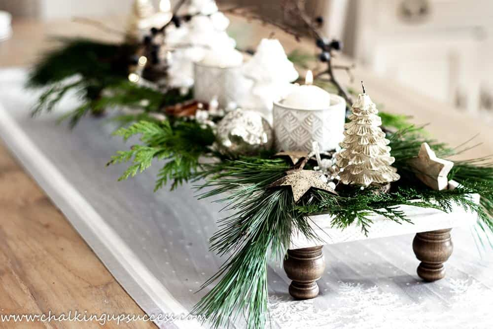 A Christmas display of white and gold candles and evergreens on a wood pedestal tray
