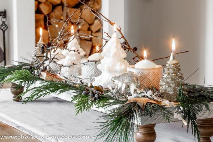 A Christmas display of white and gold candles on a wood pedestal tray