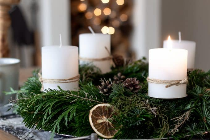 Fresh evergreen wreath with white candles