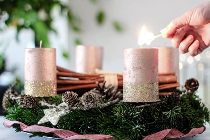 Evergreen Advent wreath with pink glitter candles being lit.