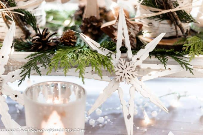Clothespin snowflakes standing against a pedestal tray on a Christmas tablescape