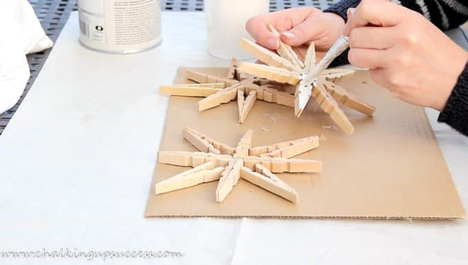 Hands painting wooden clothespin snowflakes with white paint.