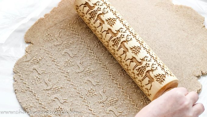 Hands rolling over Christmas biscuit dough with an embossed rolling pin