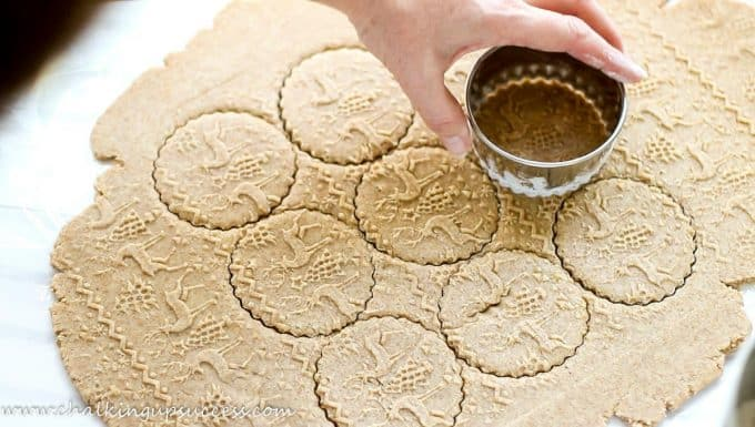 A hand cutting out cookie dough rolled with an embossed rolling pin