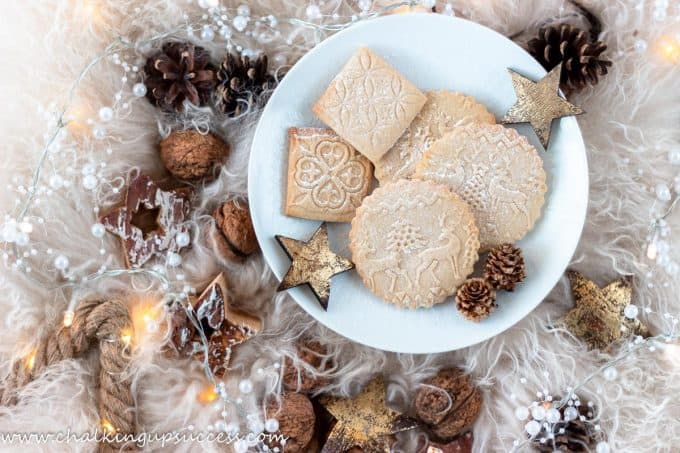 round Christmas cookies made with an embossed rolling pin on a plate srrounded by walnuts and pine cones
