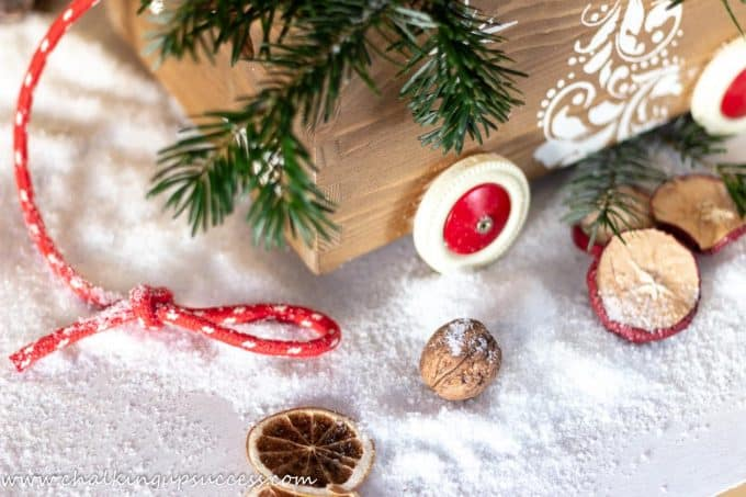 Decorating around the outside of a Christmas crate with dried apple slices, dried oranges, walnuts and artifical snow.