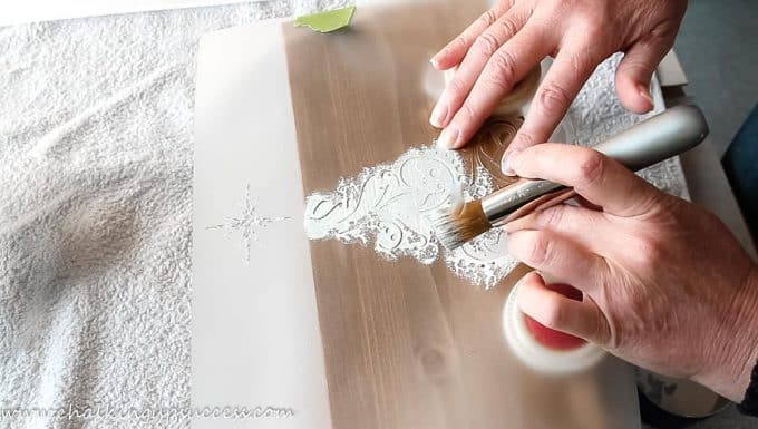 A person adding a Christmas stencil to a wooden crate with chalk paint