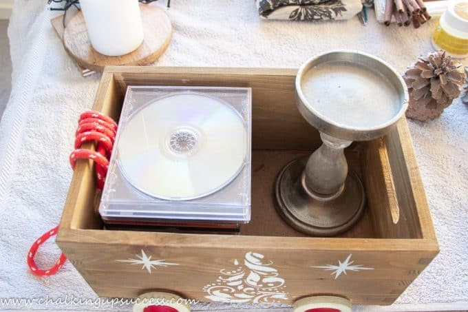 A wooden crate filled with a stack of CDs and a pedestal candlestick to add height to the decoration.