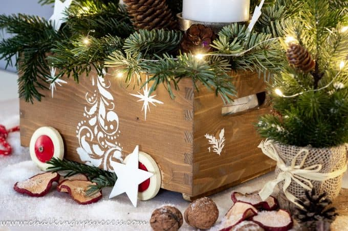 Christmas crate decorated with fresh evergreens, candles and Christmas trees.