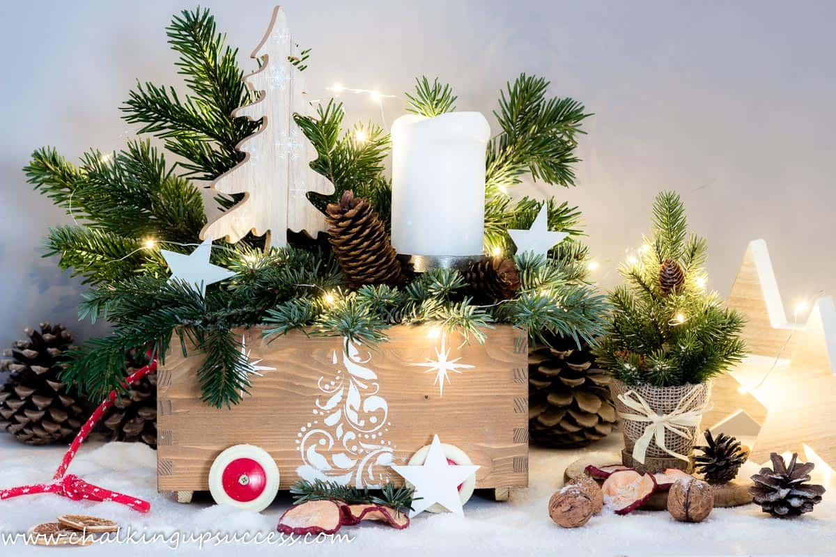 Christmas in a crate. A wooden crate filled with evergreens, candles and stars.