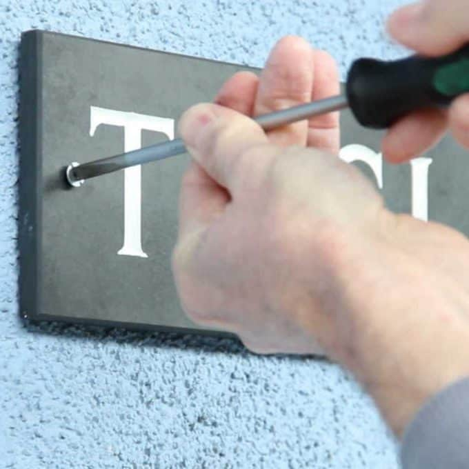 Hands installing a slate house sign with a screwdriver