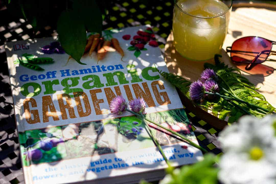 Book, 'Organic Gardening' by Geoff Hamilton on a table with flowers.