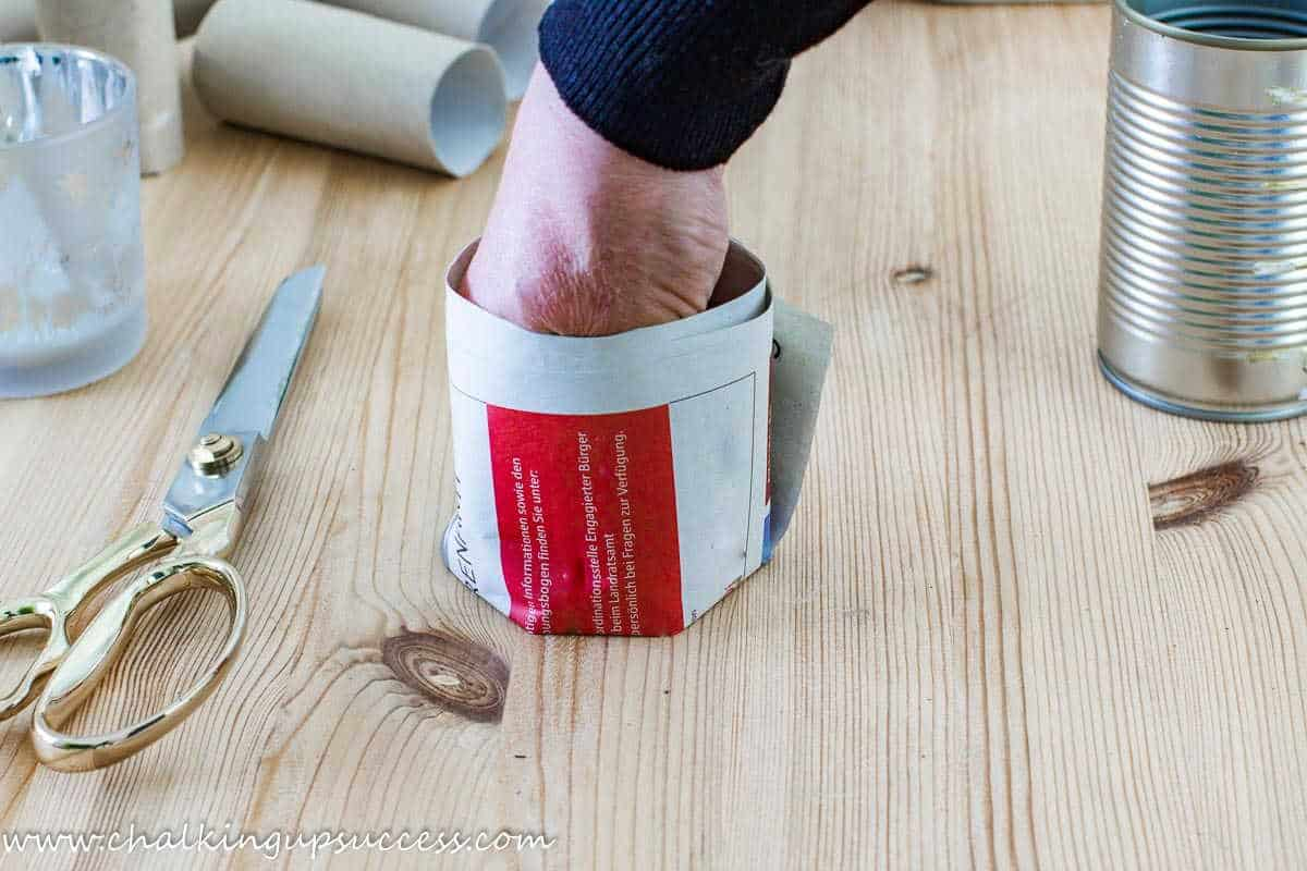 A person pushing a hand into a newspaper seedling pot to flatter the paper at the base.