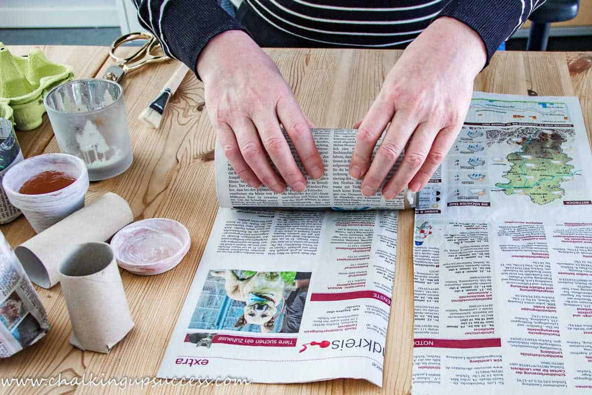 A person rolling newspaper around a tin can to make eco-friendly seed pots.