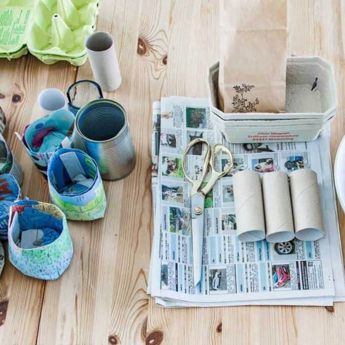 A table filled with newspapers, empty toilet rolls, egg boxes and newspaper seedling pots.