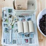 A table filled with newspapers, scissors, empty toilet rolls, egg boxes and potting soil