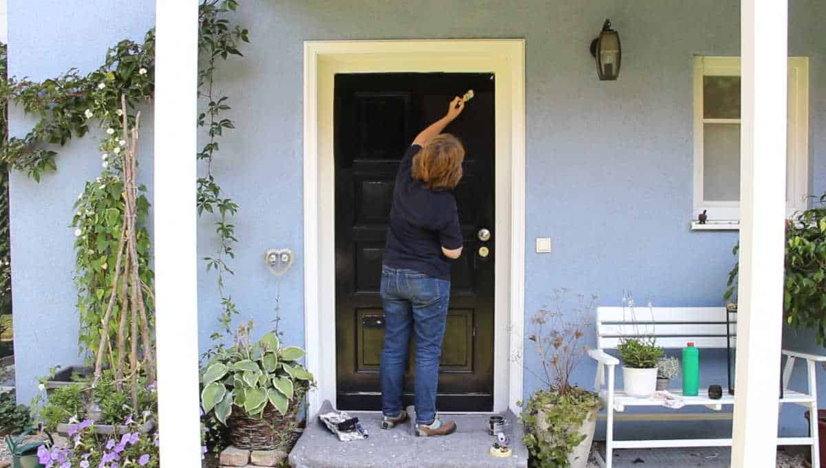 A person showing how to paint a front door black.