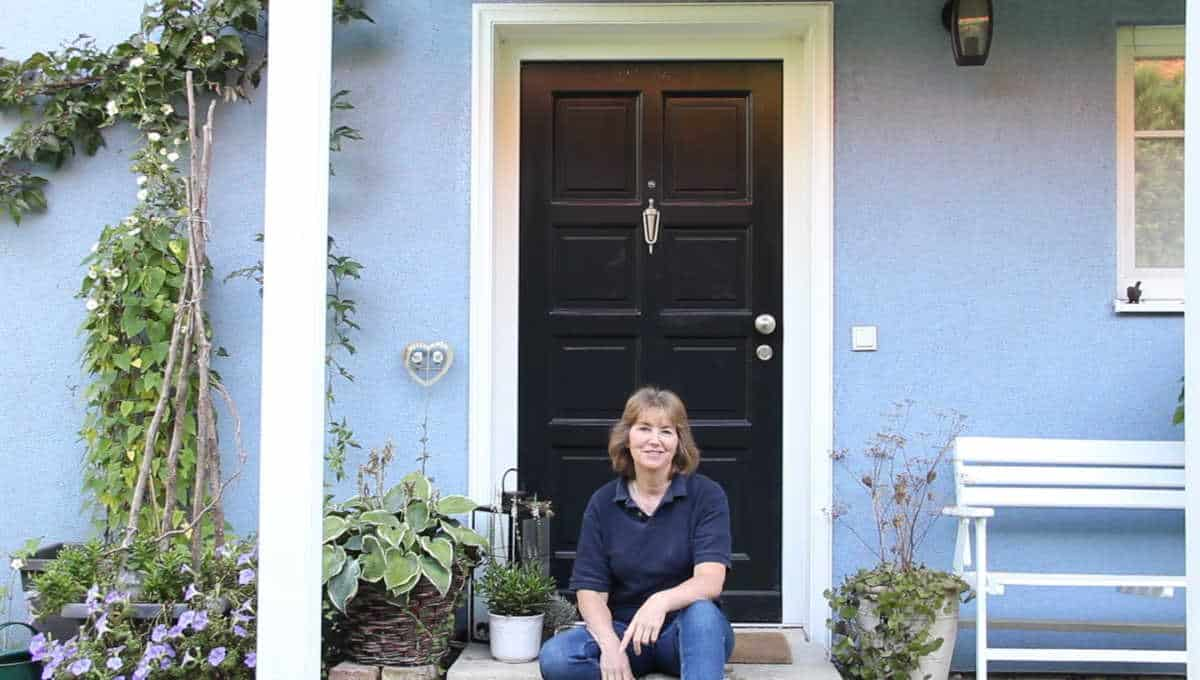 A person sitting on a doorstep in front of a black front door.