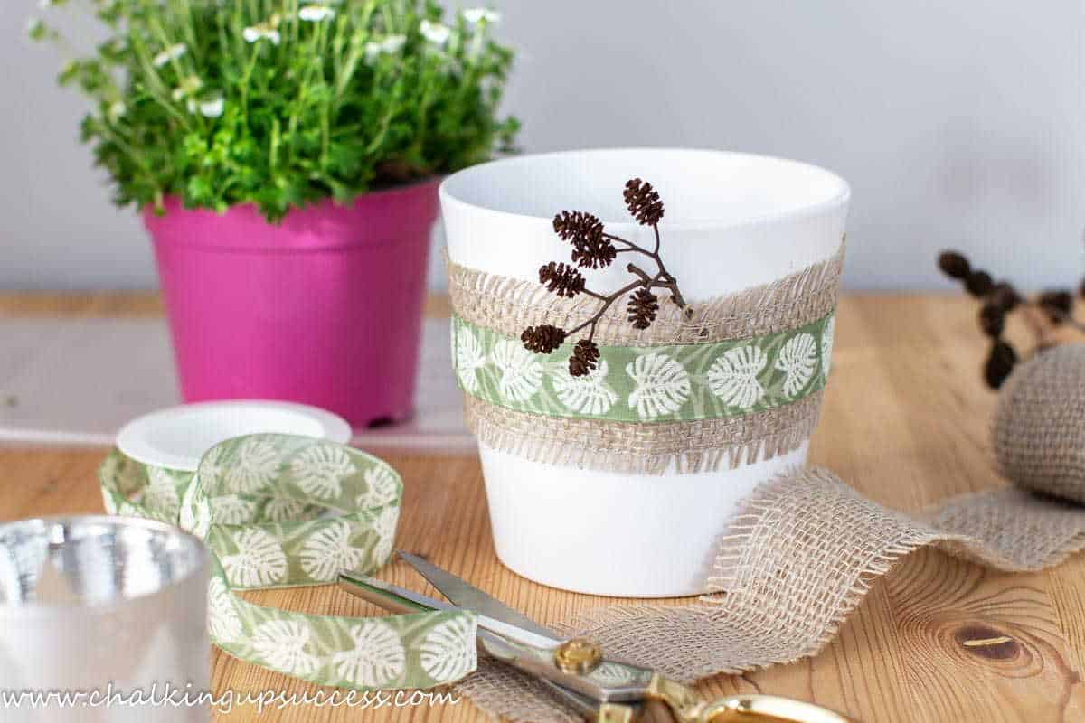 Simple decorating ideas for spring - unravelled ribbons around a white plant pot.