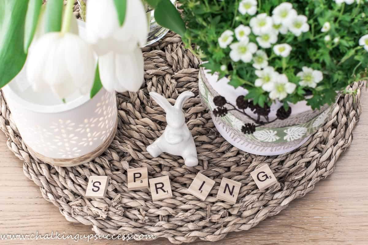 A pretty spring vignette with white flowers in a pretty pot, a white ceramic essential oil diffuser and a small white porcelain bunny rabbit sitting. The words 'Spring' are spelled out with wooden scrabble blocks.
