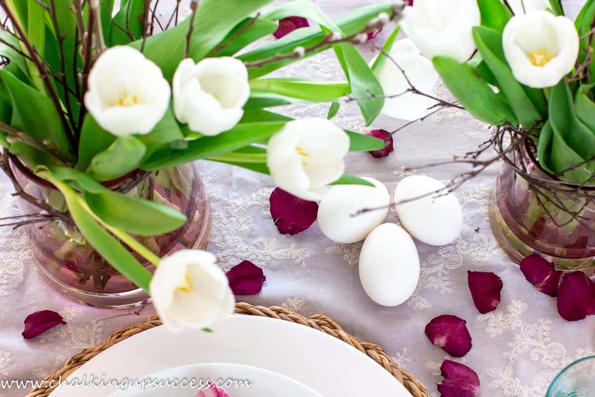 Vases filled with white tulips and three large white Easter eggs.