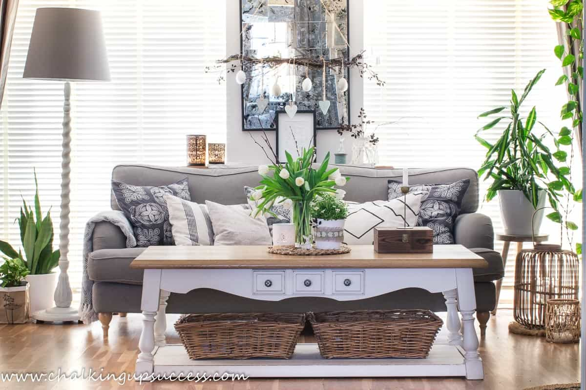 A spring home tour - lounge. A brown sofa filled with beige and black pillows sits behind a white and wood coffee table decorated with spring flowers in a glass vase and a pot of white flowers.