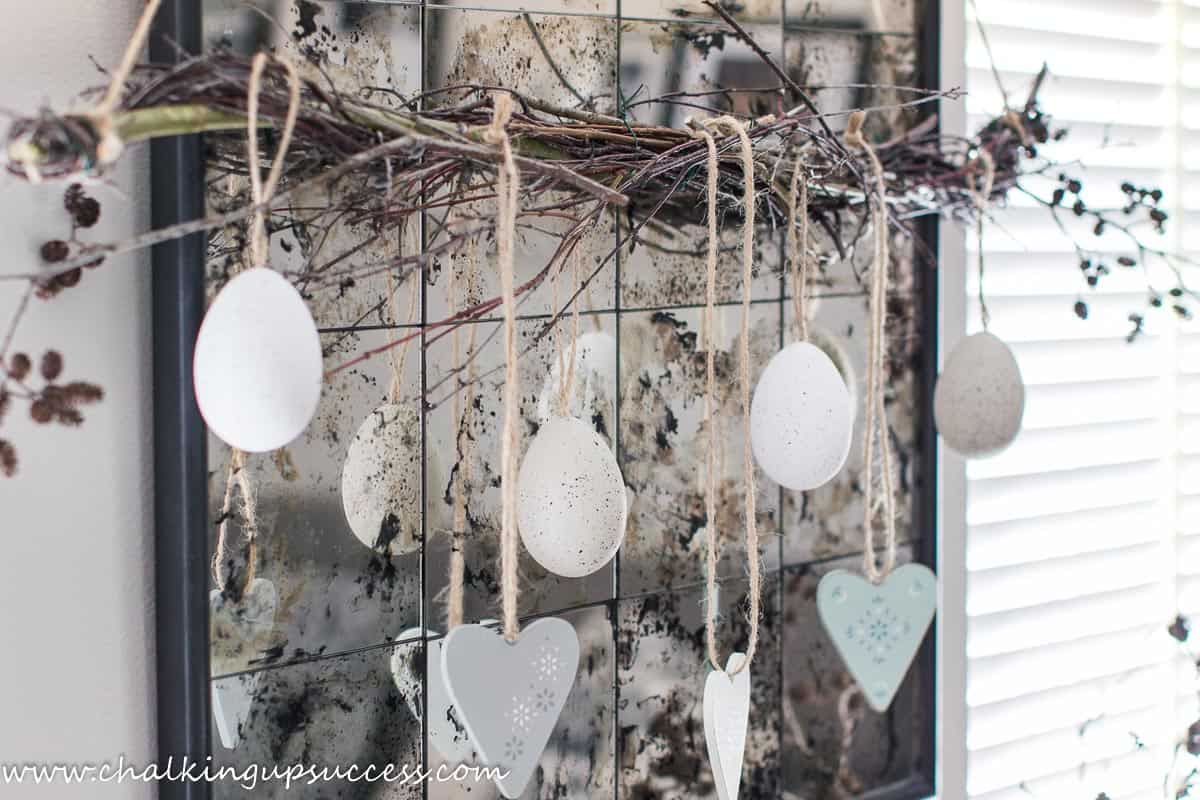 Speckled Easter eggs and hearts hanging from a garland made of willow twigs.