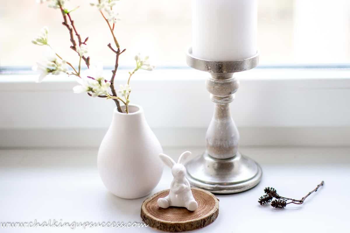 A simple Easter vignette. A sprig of Spring flowers in a small white bud vase next to a large white church candle and a small white porcelain rabbit.