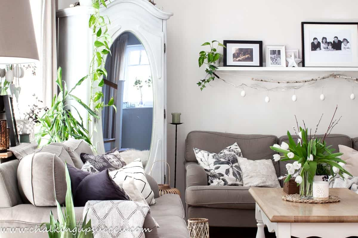 Spring home tour - lounge. Showing two brown sofas, a white and wood coffee table adorned with a vase of white tulips and an essential oil diffuser.