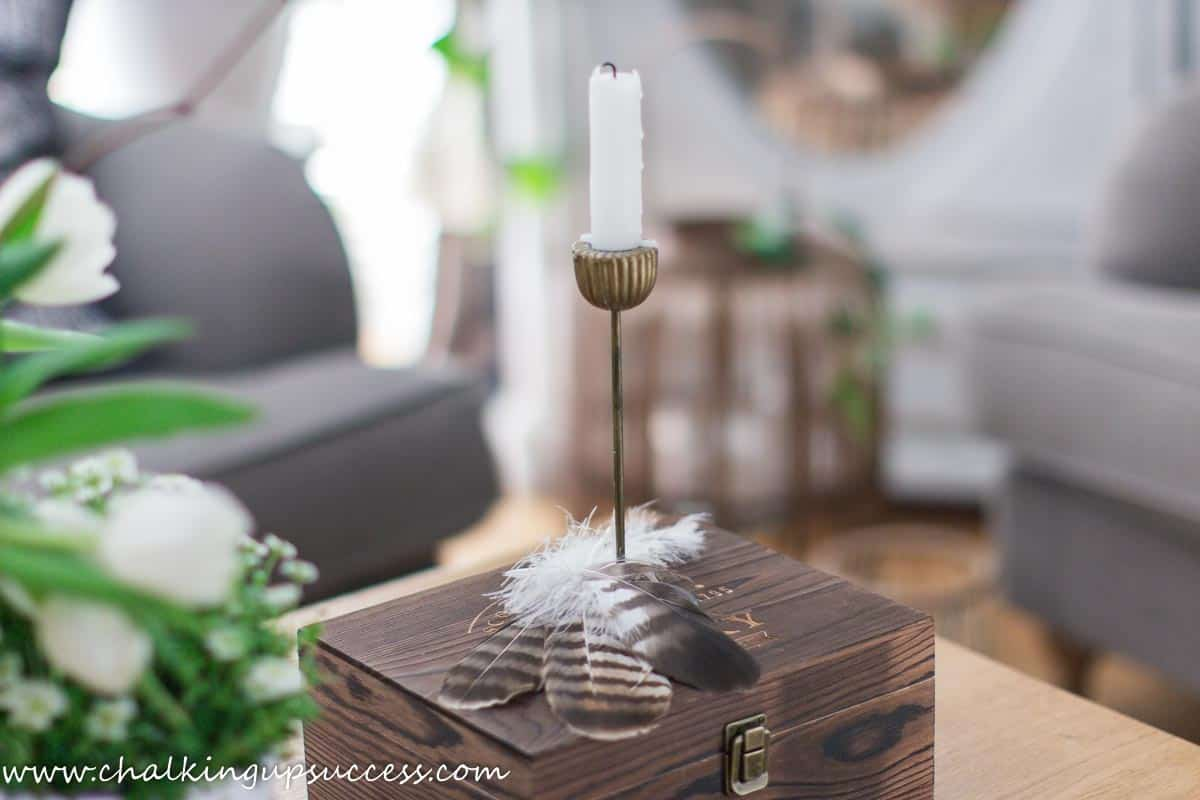 Spring home tour - a white candle in a candlestick standing on a small brown box. The base of the candle holder is covered with large brown barn owl feathers.