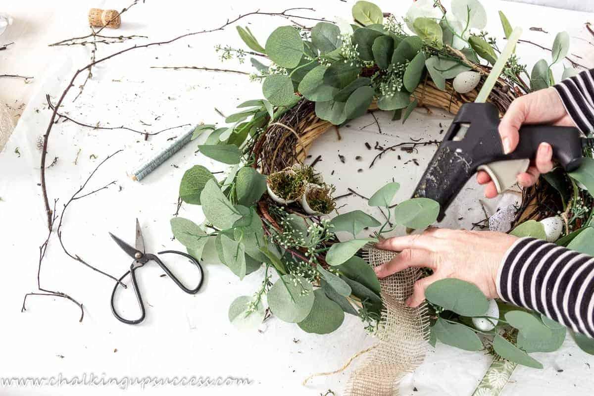A person using a glue gun to glue burlap ribbon to a DIY spring wreath