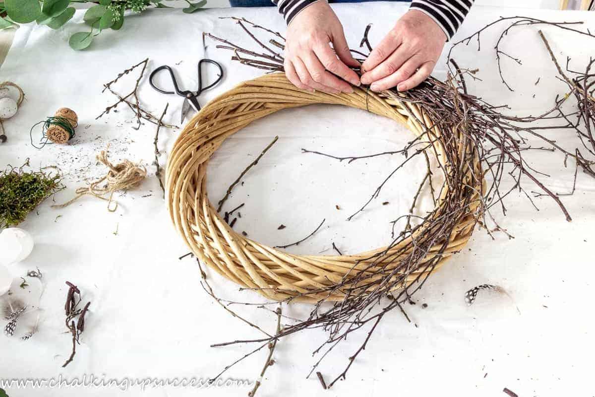 Hands tying birch twigs to a twisted wicker base wreath.