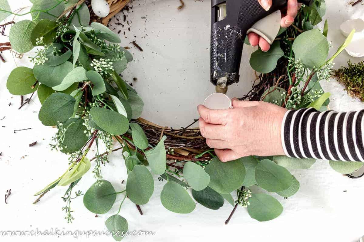 Hands using a glue gun to glue eggshells to a DIY spring wreath